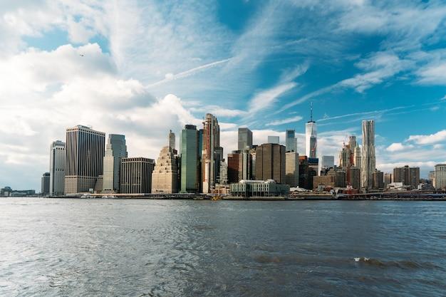 Bunte fotolandschaft von new york city mit strahlend blauem himmel und wellen des meeres