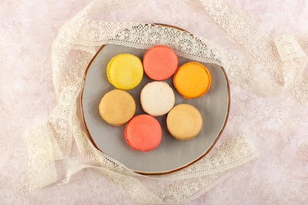 Bunte französische macarons der draufsicht innerhalb der runden platte auf der rosa schreibtischkuchen-kekszuckerfarbe