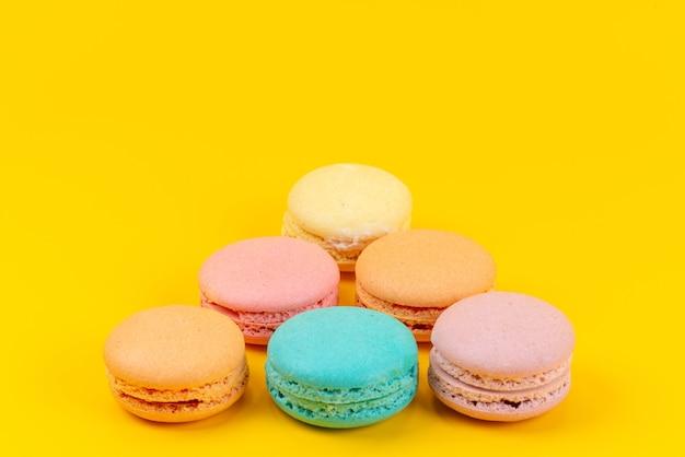 Bunte französische macarons der vorderansicht, die köstlich auf gelber kuchenkeksfarbe köstlich sind