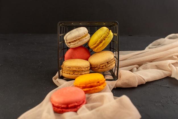 Bunte französische macarons der vorderansicht, die köstlich und im korb auf der dunklen oberfläche gebacken werden