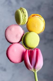 Bunte französische macarons und rosafarbene tulpe. nahaufnahme