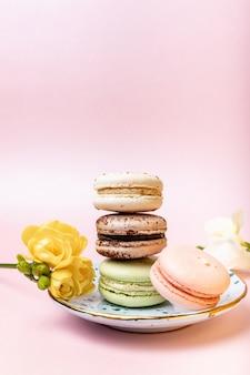 Bunte französische makronen mit freesie auf rosa