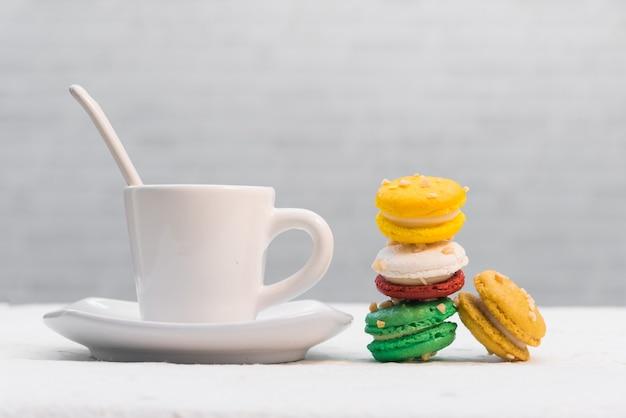 Bunte französische makronen mit tasse kaffee auf weißem hintergrund