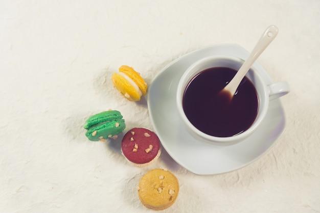 Bunte französische makronen mit tasse kaffee-weinlesefarbe