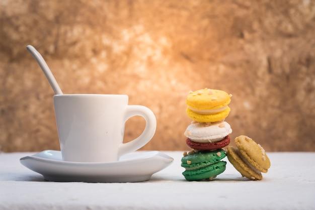 Bunte französische makronen mit tasse kaffee