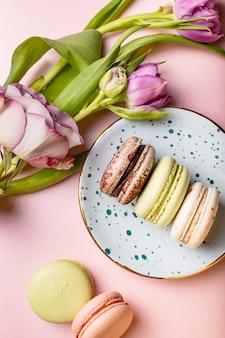 Bunte französische makronen mit tulpen und rose auf rosa, flacher lage
