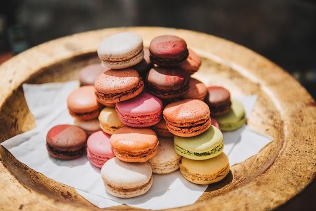 Bunte französische makronen oder macarons auf einem goldenen teller
