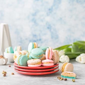 Bunte französische oder italienische macarons stapeln sich auf rotem teller. dessert zum servieren mit nachmittagstee oder kaffeepause. schöner essenshintergrund