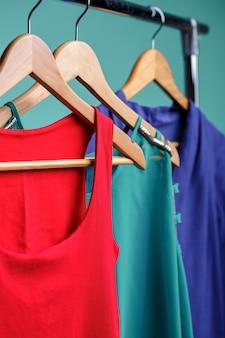 Bunte frauenhemden auf holzbügeln auf rang auf blauem hintergrund. rgb-konzept