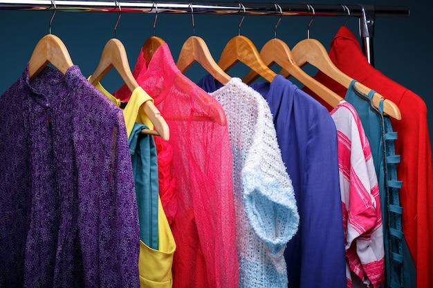 Bunte frauenkleider auf hölzernen kleiderbügeln auf gestell auf blauem hintergrund. frauenschrank nahaufnahme
