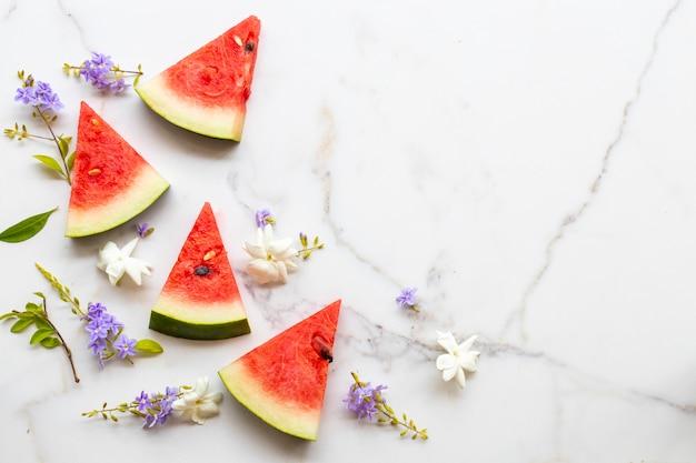 Bunte frische früchte wassermelone gesunde lebensmittel für die gesundheitsfürsorge mit blumen