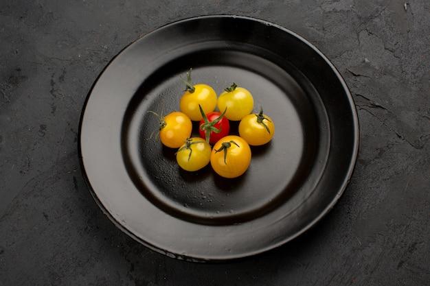Bunte frische reife tomaten innerhalb der schwarzen platte auf einem grau