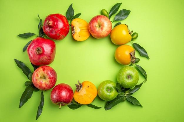 Bunte früchte bunte früchte mit blättern auf dem grünen tisch