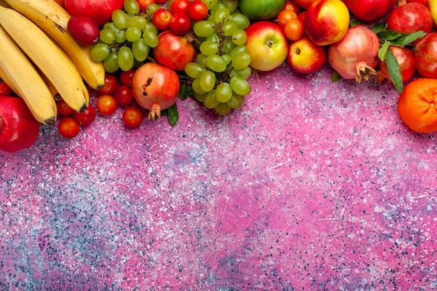 Bunte früchte der frischobstzusammensetzung der draufsicht auf hellrosa oberfläche