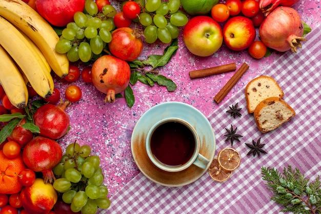 Bunte früchte der frischobstzusammensetzung der draufsicht mit tasse tee auf hellrosa schreibtisch