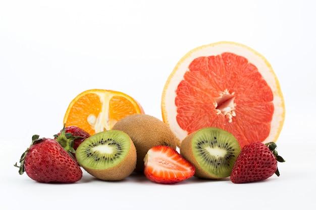 Bunte früchte frische milde saftige früchte wie grapefruit und erdbeeren isoliert auf weißem schreibtisch