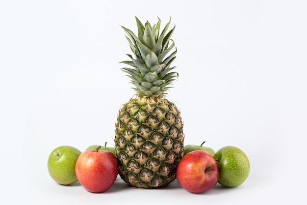 Bunte früchte reife saftige ananas und bunte äpfel auf einem weißen schreibtisch