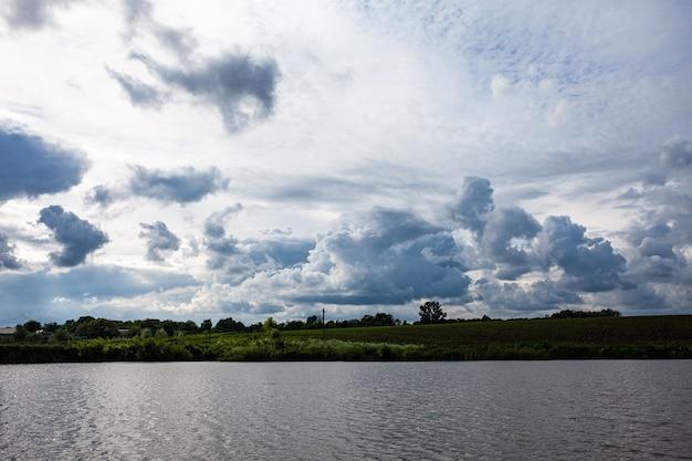Bunte frühlingslandschaft am see sonniger tag viele wolken am himmel blick auf den see bei sonnenaufgang