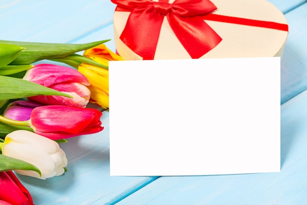 Bunte frühlingstulpe blüht mit dekorativem giftbox und freiem raum auf hellblauem