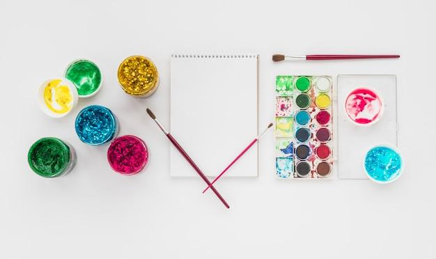 Bunte funkelnfarbe und wasserfarbpalette mit gewundenem tagebuch auf weißem hintergrund