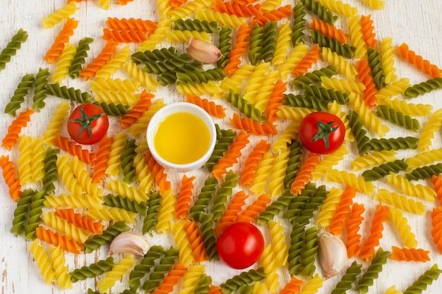 Bunte fusilli-nudeln mit öl und tomaten