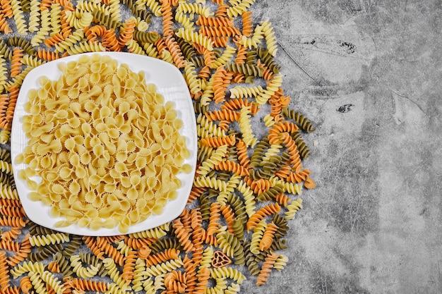 Bunte fusilli und schüssel mit roher pasta auf marmorhintergrund