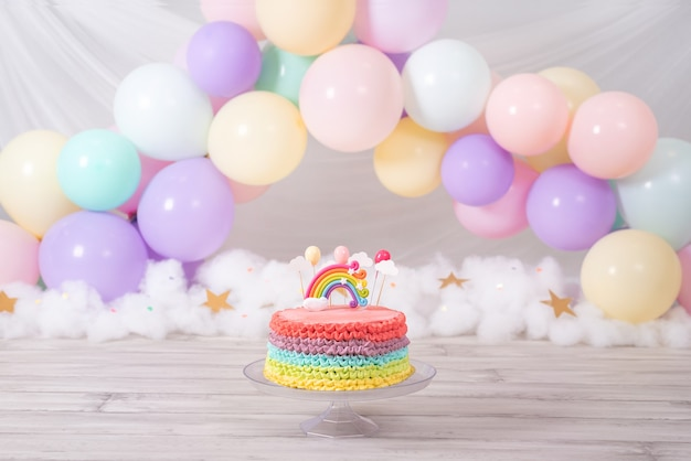 Bunte geburtstagstorte. regenbogenkuchen mit pastellfarbenen luftballons. geburtstagsfeier.