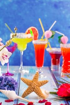 Bunte gemischte cocktails im tropischen blauen holz