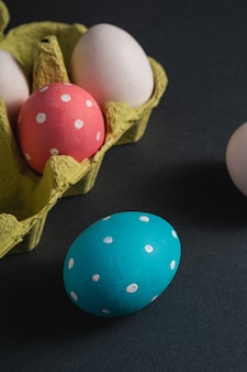 Bunte gepunktete ostereier in der eierablage auf dunkelgrauem schwarzem einfachem hintergrund, grußkarte, winkelansicht