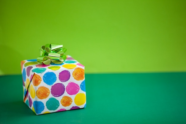 Bunte geschenkbox auf kalkfarbhintergrund. feiertagsgrußkarte