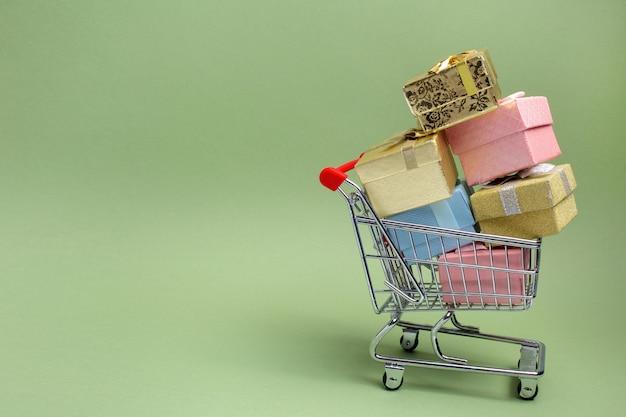 Bunte geschenkbox, supermarkt-einkaufswagen auf grünem hintergrund