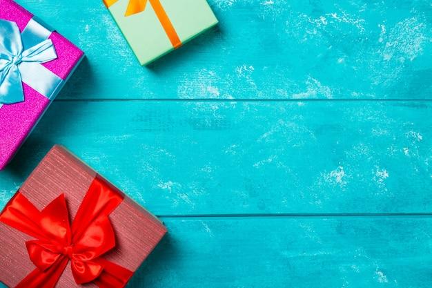 Bunte geschenkboxen auf blauem hölzernem hintergrund