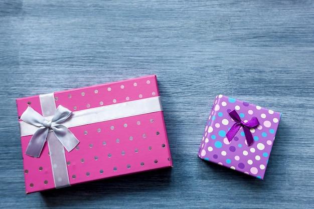 Bunte geschenkboxen in rosa und lila farbe auf einem holztisch.