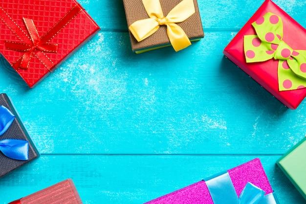 Bunte geschenkboxen mit bändern auf schönem blauem hölzernem hintergrund.