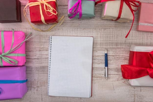 Bunte geschenkboxen mit geöffnetem notizblock. neujahrsplanung. neuer anfang