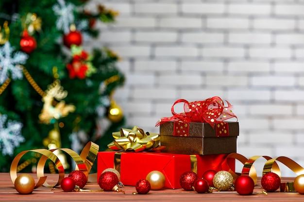 Bunte geschenkboxen mit heller farbbandfliege an der ecke des holztisches vor dem voll dekorativen schönen heiligabend-kiefer und der backsteinmauer in unscharfem hintergrund.