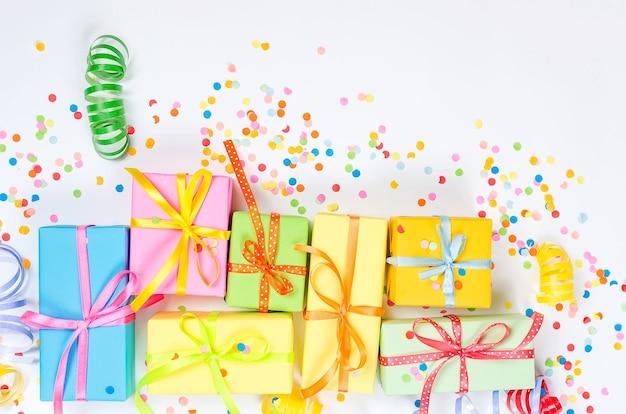 Bunte geschenkboxen, papierkonfetti und gewirbelte party-serpentine auf einem weißen hintergrund