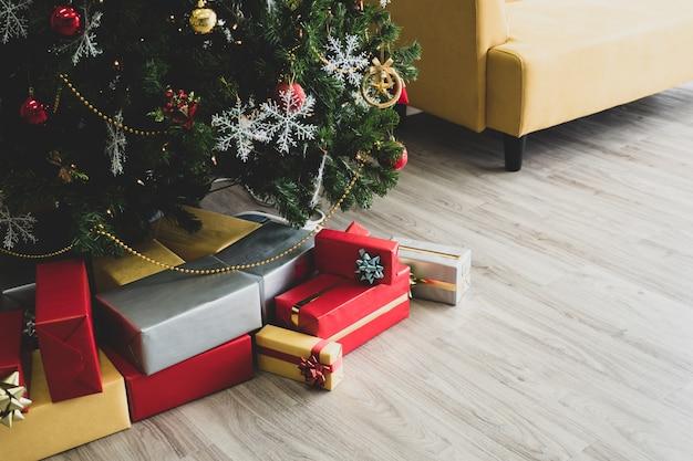 Bunte geschenkboxen unter verziertem weihnachtsbaum auf bretterboden.