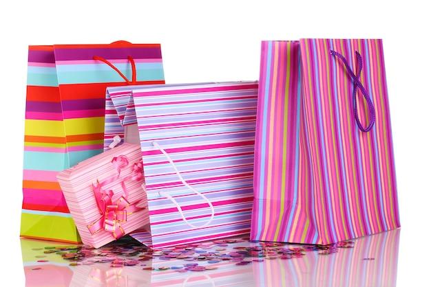 Bunte geschenktüten und geschenke mit konfetti isoliert auf weißer oberfläche