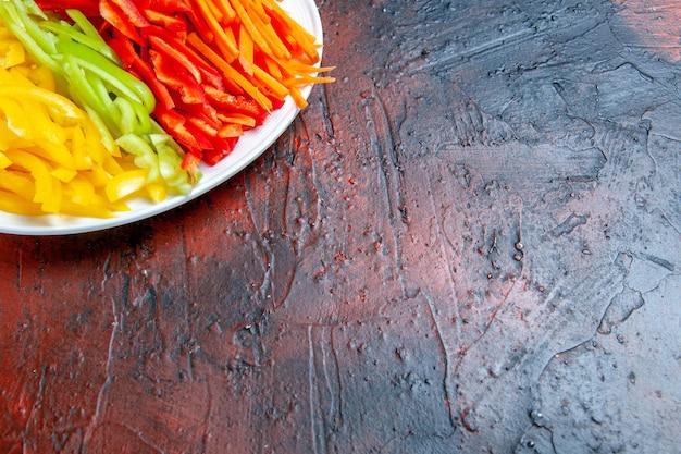 Bunte geschnittene paprika der oberen hälfteansicht auf weißem teller auf dunkelrotem tisch mit freiem platz