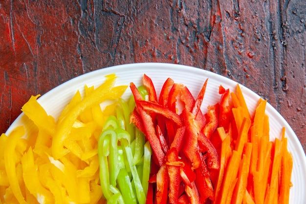 Bunte geschnittene paprika der oberen hälfteansicht auf weißem teller auf dunkelrotem tisch