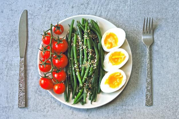 Bunte, gesunde lebensmittel. flatlay. buddha-schale mit eiern, grünen bohnen und kirschtomaten.