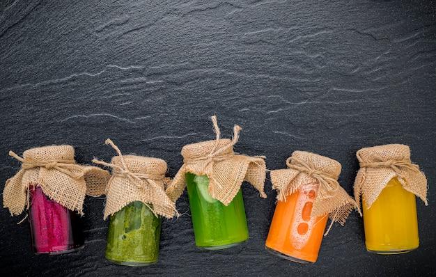 Bunte gesunde smoothies und säfte in den flaschen auf dunklem steinhintergrund mit kopienraum.