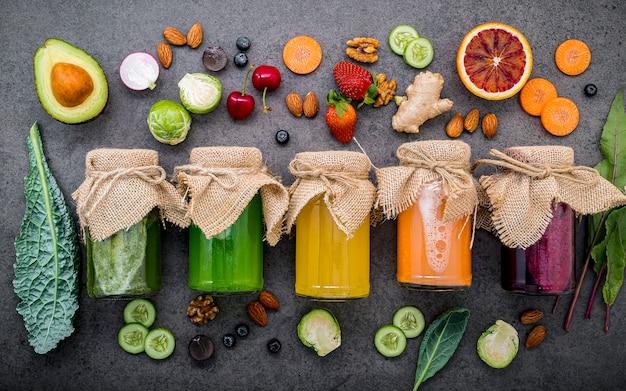 Bunte gesunde smoothies und säfte in den flaschen mit frischer tropischer frucht und superfoods auf dunklem steinhintergrund mit kopienraum.