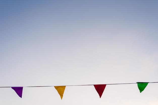 Bunte girlanden, die im wind gegen ein ideal des blauen himmels für das verzieren eines geburtstages wellenartig bewegen.