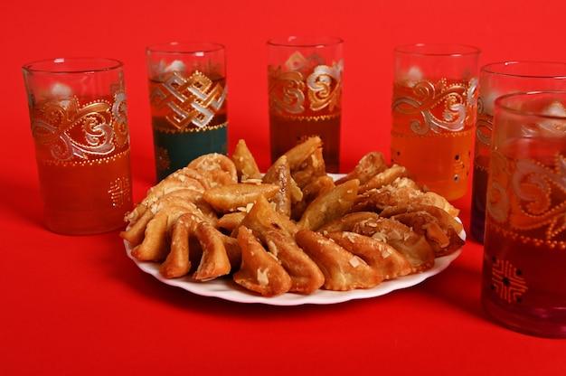 Bunte gläser minztee in marokkanischer tradition, mit schöner dekoration und einem teller mit arabischem süßem dessert im vordergrund. auf rotem hintergrund mit kopienraum isoliert