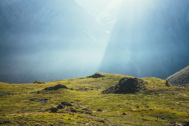 Bunte grüne landschaft mit felsen und hügeln auf dem hintergrund der riesigen bergwand im sonnenlicht. minimalistische, lebendige, sonnige landschaft mit sonnenstrahlen und sonneneruption. minimaler alpenblick. szenischer minimalismus.