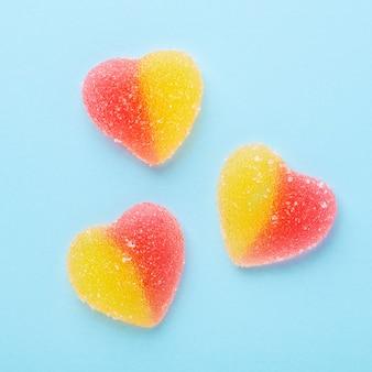 Bunte gummiartige herzen auf blauem tisch. gelee-süßigkeiten. draufsicht.