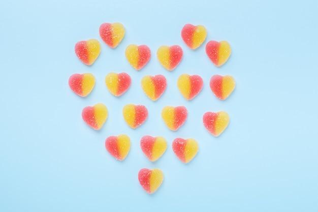 Bunte gummiartige herzen auf blauem tisch. gelee süßigkeiten in form des herzens.