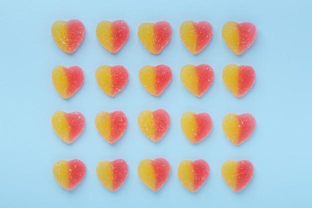 Bunte gummiartige herzen auf blauem tisch. gelee-süßigkeiten.